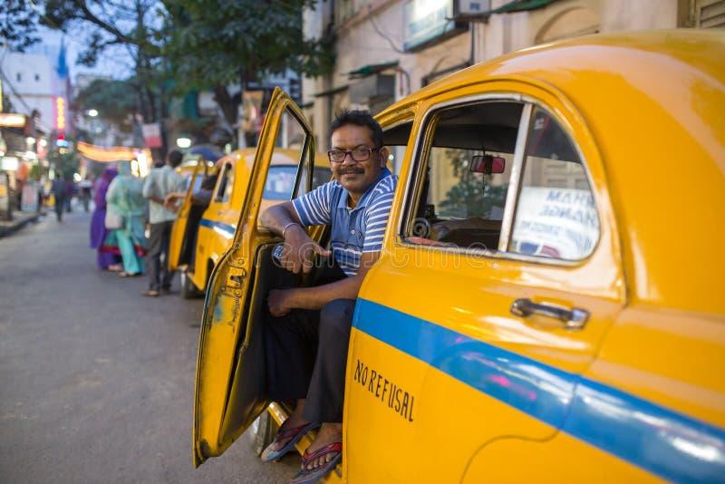 Retrato de um taxista indiano com seu táxi antigo do amarelo do oldtimer nas ruas de Kolkata foto de stock