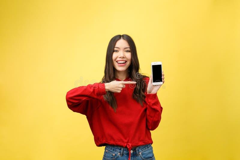 Retrato de um telefone celular da terra arrendada da menina e de um dedo ocasionais alegres apontar isolados afastado sobre o fun imagens de stock