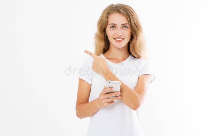 Retrato de um telefone celular da terra arrendada da menina e de um dedo ocasionais alegres felizes apontar isolados afastado sob fotos de stock royalty free