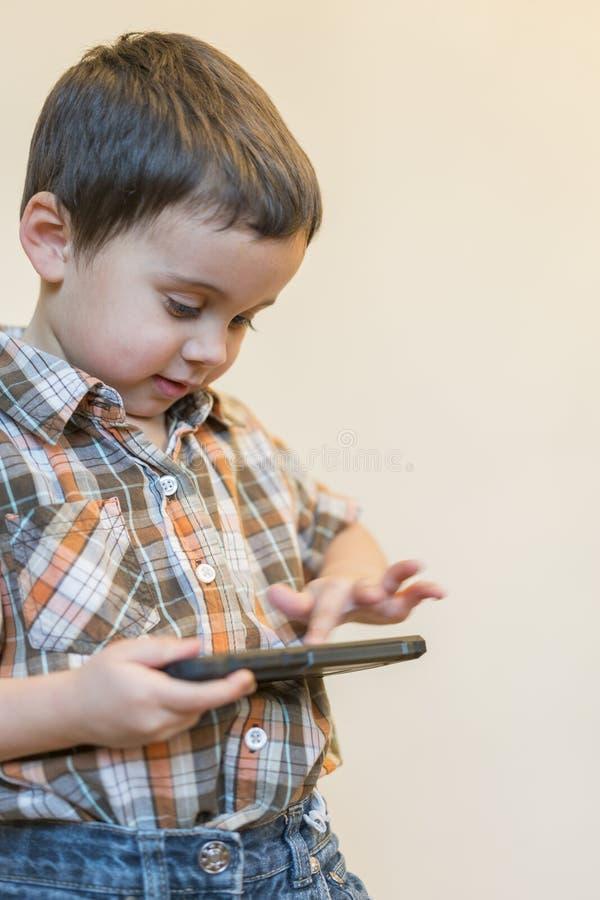 Retrato de um telefone celular de sorriso da terra arrendada do rapaz pequeno isolado sobre o fundo claro Crian?a bonito que joga fotos de stock royalty free