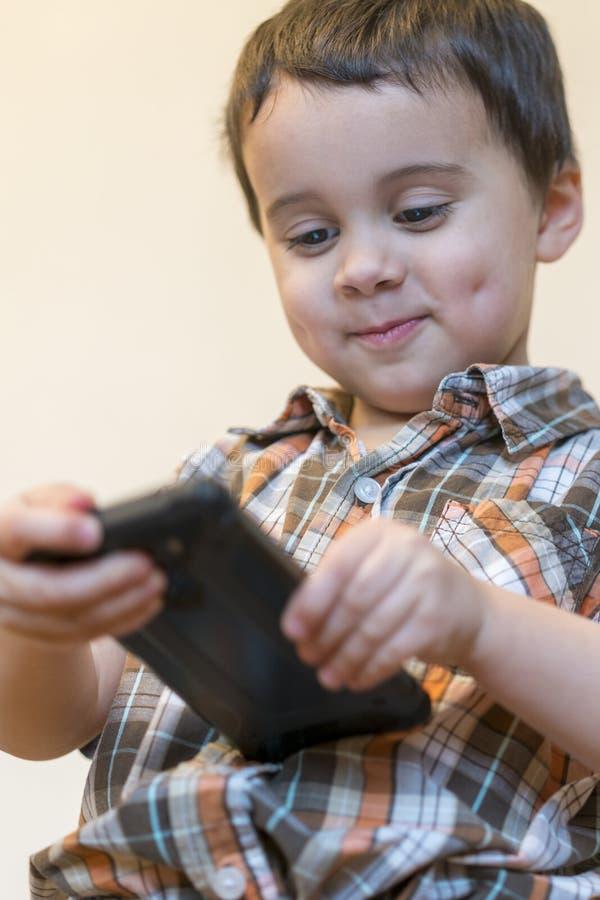 Retrato de um telefone celular de sorriso da terra arrendada do rapaz pequeno isolado sobre o fundo claro Crian?a bonito que joga fotografia de stock