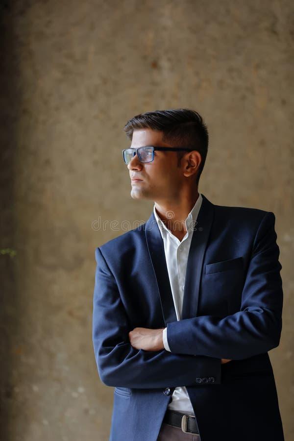 Retrato de um terno vestindo e de uns espetáculos do homem de negócios bem sucedido indiano novo foto de stock