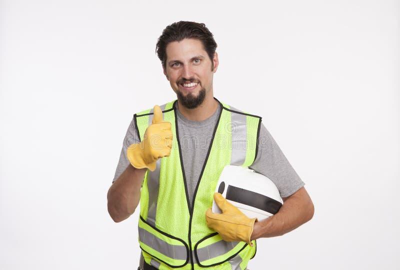 Retrato de um trabalhador da construção que mostra os polegares acima imagens de stock