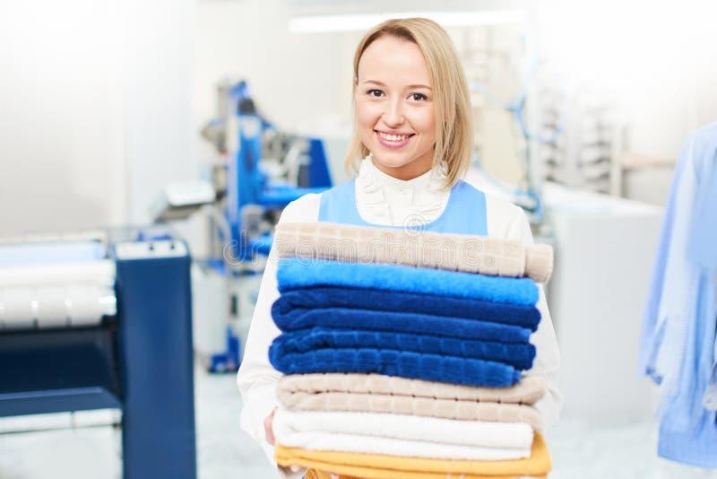 Retrato de um trabalhador da lavanderia da menina que guarda uma toalha limpa fotos de stock royalty free