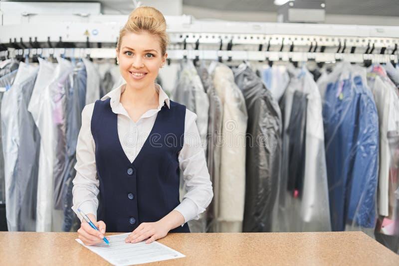 Retrato de um trabalhador da lavanderia no fundo da roupa em ganchos imagem de stock royalty free