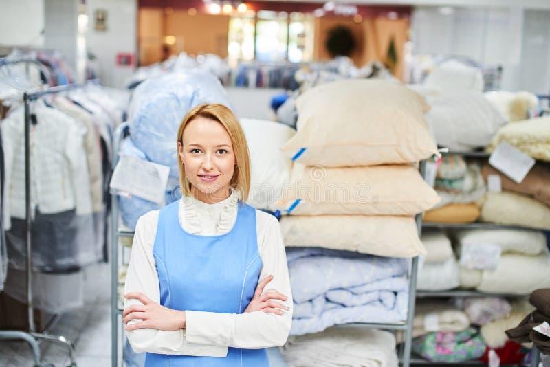 Retrato de um trabalhador da menina em uma lavanderia do armazém com roupa limpa imagens de stock royalty free
