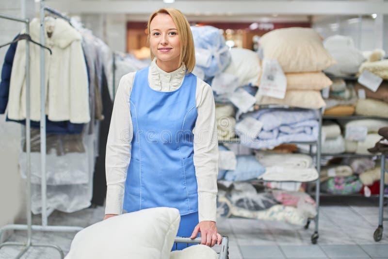 Retrato de um trabalhador da menina em uma lavanderia do armazém com roupa limpa imagens de stock