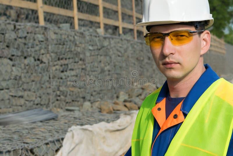 Retrato de um trabalhador em um capacete branco e em uns vidros amarelos protetores, à esquerda um lugar para sua inscrição fotografia de stock