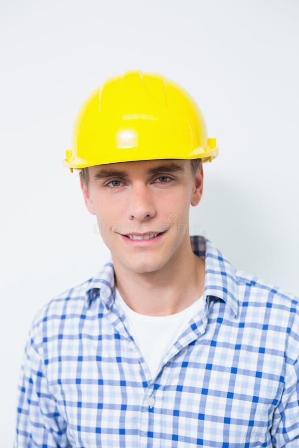 Retrato de um trabalhador manual de sorriso que veste um capacete de segurança amarelo fotografia de stock