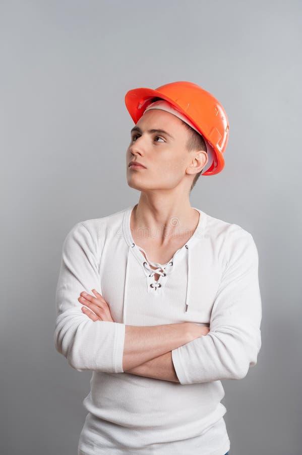 Retrato de um trabalhador seguro novo no capacete fotografia de stock royalty free