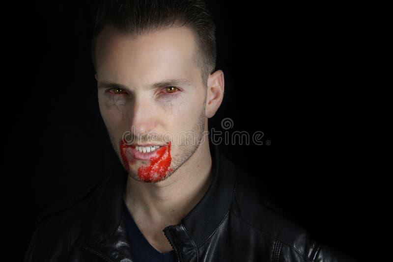 Retrato de um vampiro novo com sangue nos bordos imagens de stock royalty free