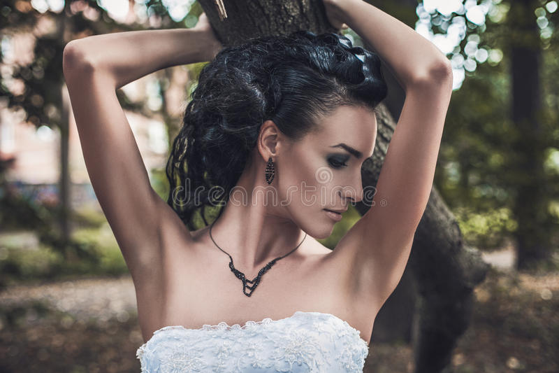 Retrato de um vestido de casamento moreno bonito da noiva no parque imagens de stock royalty free
