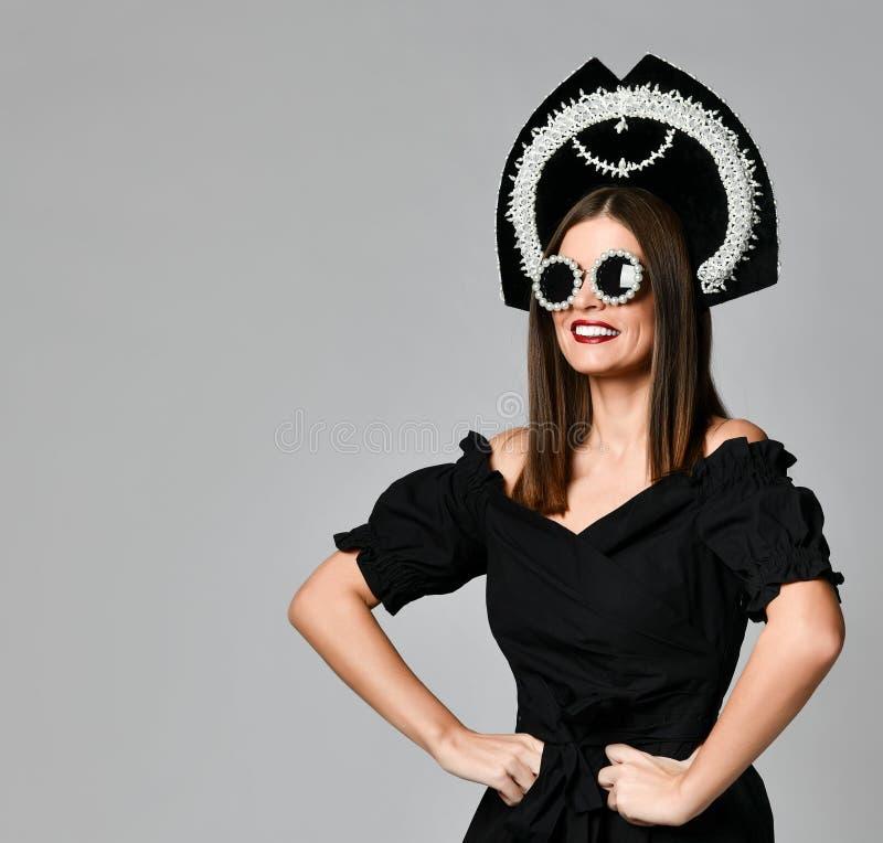 Retrato de um vestido preto moreno elegante, de uns óculos de sol pretos, de um tampão do kokoshnik, de um cabelo longo e de uma  fotografia de stock