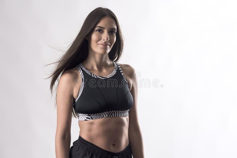 Retrato de uma atleta esportiva atraente em cima preto com grandes abdominais sorrindo à câmera imagens de stock