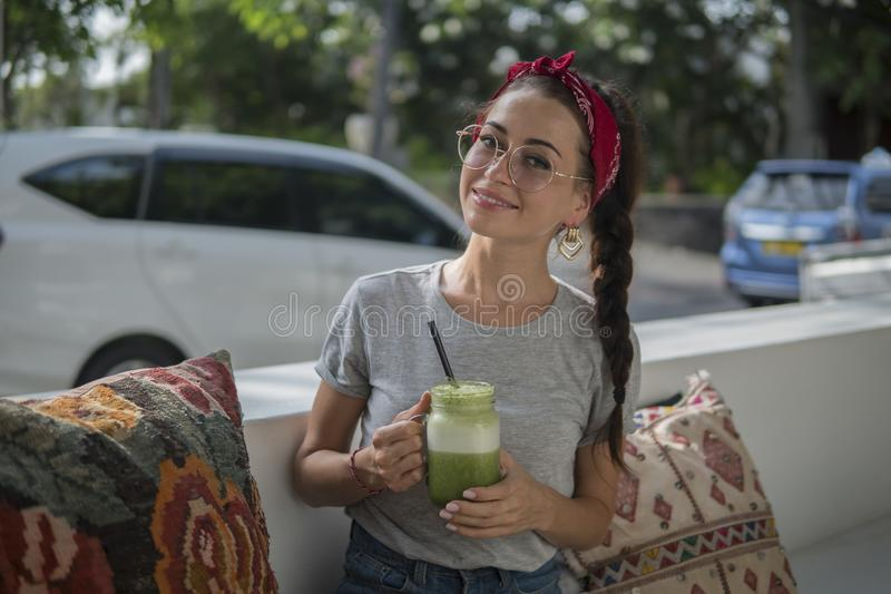 Retrato de uma beleza de cabelo escuro nova com uma trança que relaxa no café exterior perto da estrada, morena em um pano vermel imagem de stock