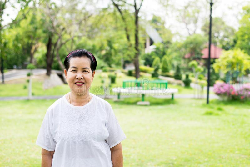 Retrato de uma c?mera asi?tica idosa da posi??o e da vista da mulher no parque, feliz e no sorriso fotos de stock royalty free