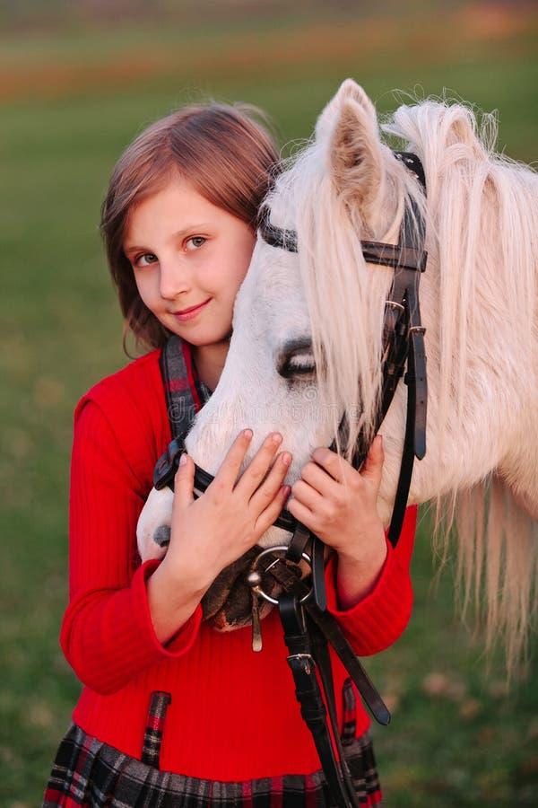 Retrato de uma cabeça e de olhar de cavalo branco pequena do bnimaet do modelo da moça a câmera fotografia de stock