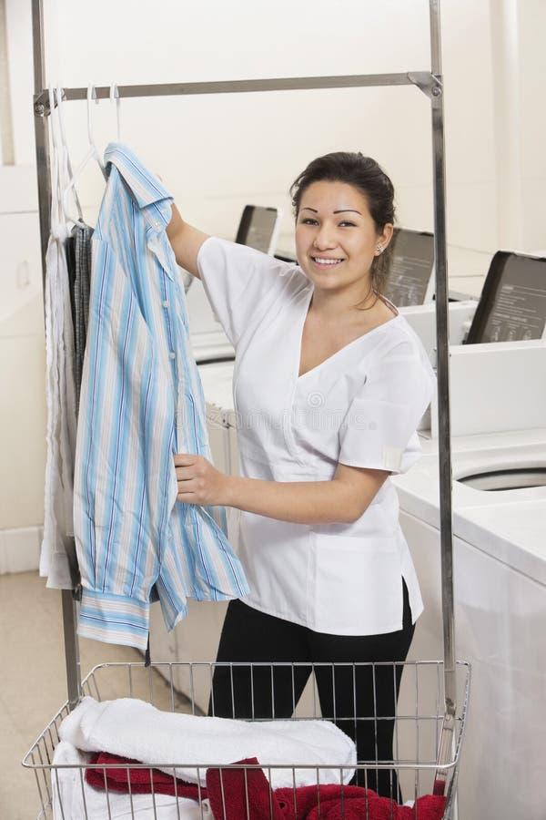 Retrato de uma camisa de suspensão da jovem mulher feliz na frente das máquinas de lavar na lavagem automática imagens de stock royalty free