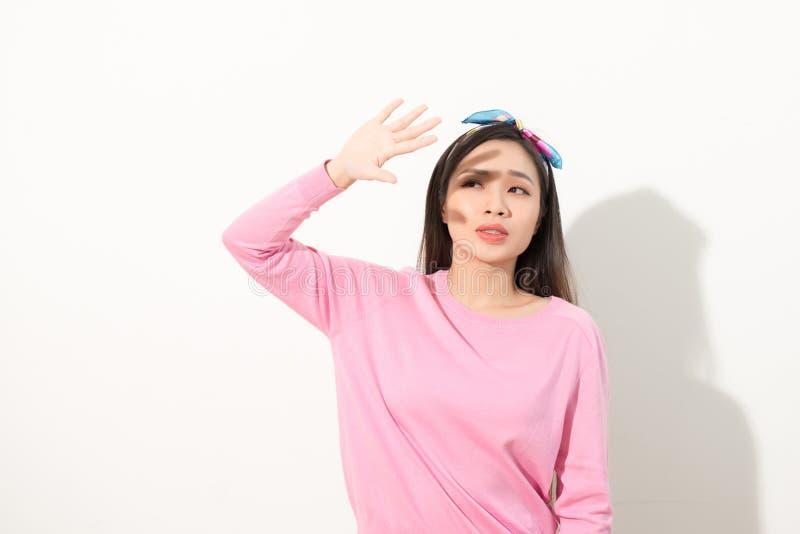 Retrato de uma cara asiática bonita da coberta da menina à mão da luz brilhante do sol mulher em um vestido cor-de-rosa que prote imagens de stock