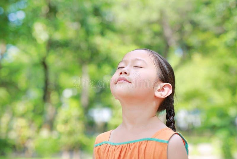 Retrato de uma criança asiática feliz fecha os olhos no jardim com ar fresco de Breathe da natureza Feche a menina relaxe no parq imagens de stock