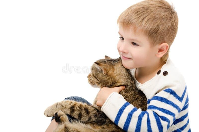 Retrato de uma criança bonito que abraça um gato imagens de stock