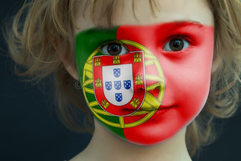 Retrato de uma criança com uma bandeira pintada de Portugal fotos de stock royalty free