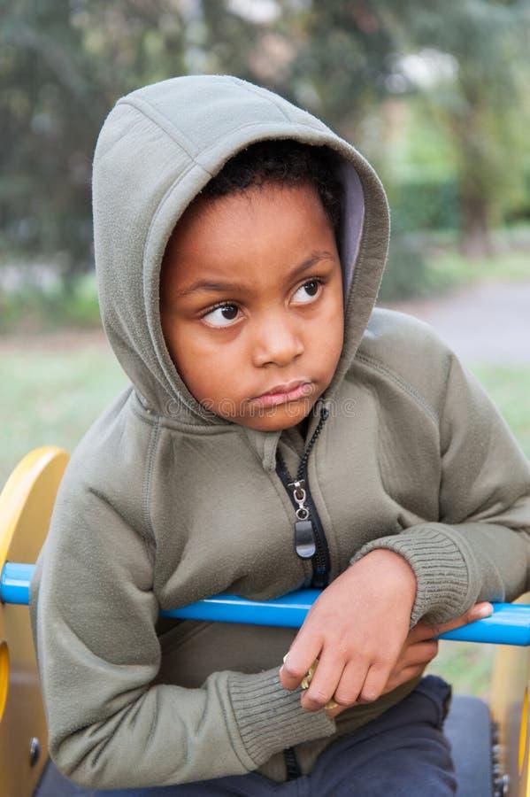 Retrato de uma criança da cor com a capa sobre sua cabeça imagens de stock