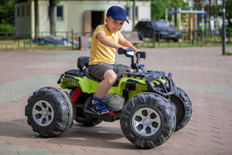 Retrato de uma criança em um ATV O menino conduz um carro em um parque de diversões foto de stock
