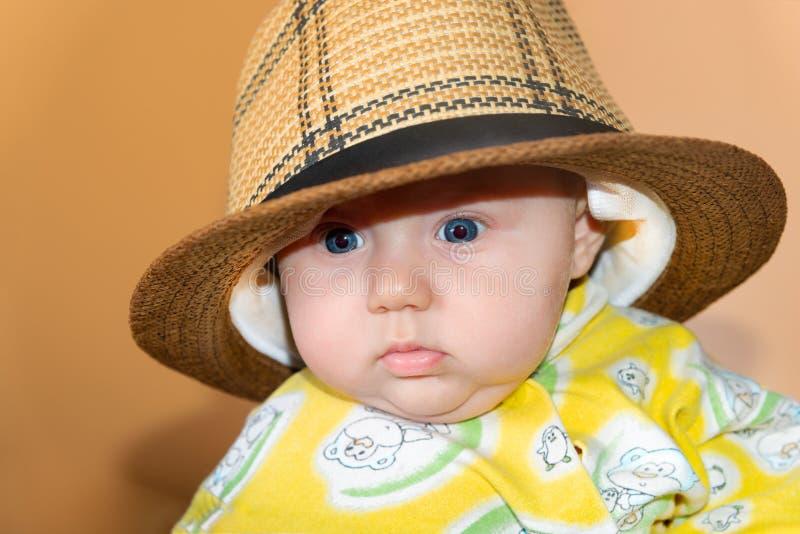 Retrato de uma criança, uma menina em um chapéu de palha, no estúdio em um fundo bege fotografia de stock