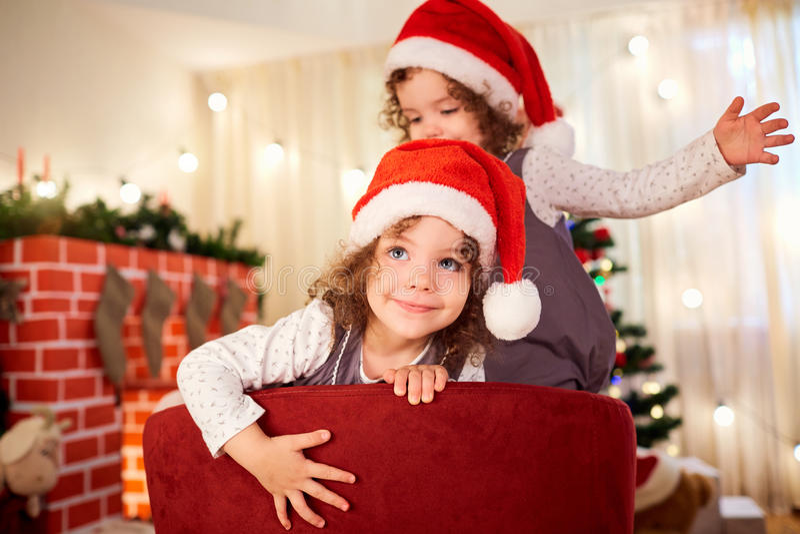 Retrato de uma criança no Natal Menina bonito encaracolado no chapéu a de Santa foto de stock royalty free