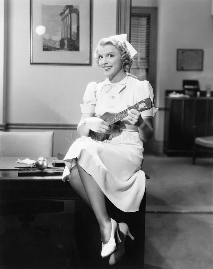 Retrato de uma enfermeira fêmea que senta-se em uma tabela e que joga uma guitarra (todas as pessoas descritas não são nenhum da  foto de stock