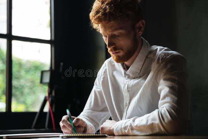 Retrato de uma escrita concentrada do homem do ruivo em um caderno fotos de stock royalty free