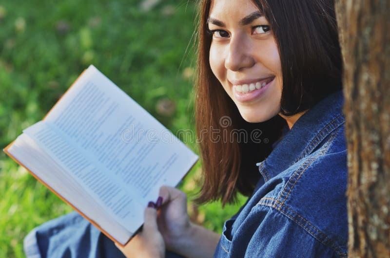 Retrato de uma estudante bonita nova da aparência asiática que lê o assento na grama verde fotos de stock