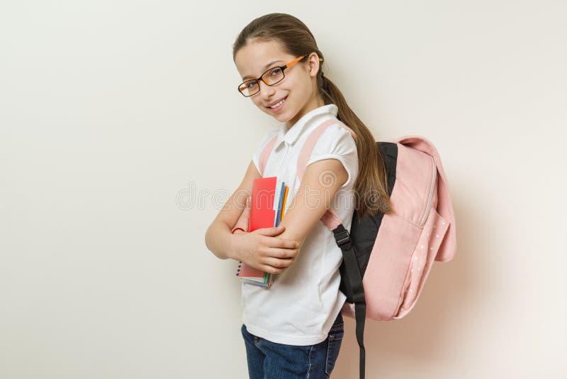 Retrato de uma estudante de sorriso 10 anos velha com vidros, com uma trouxa, cadernos imagens de stock royalty free