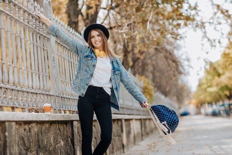 Retrato de uma estudante de sorriso encantador do moderno com o cabelo marrom que veste um chapéu, uma trouxa e uns fones de ouvi fotografia de stock