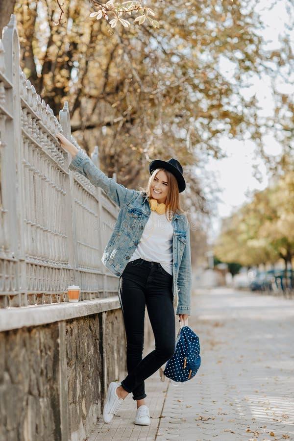 Retrato de uma estudante de sorriso encantador do moderno com o cabelo marrom que veste um chap?u, uma trouxa e uns fones de ouvi fotografia de stock royalty free