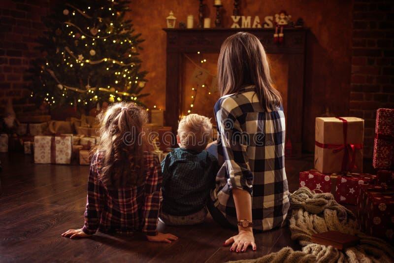 Retrato de uma família alegre que realxing em uma noite do inverno imagens de stock royalty free
