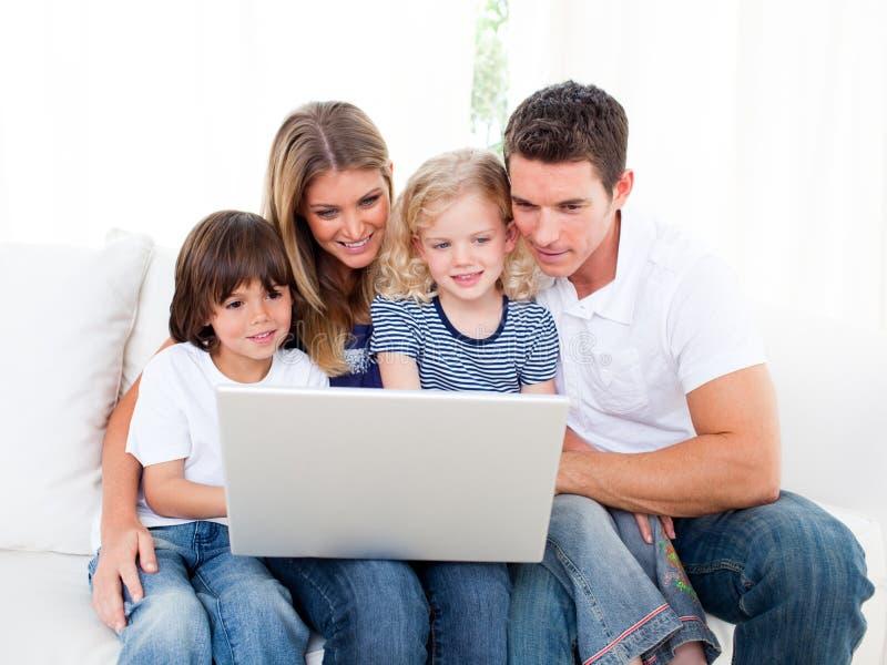 Retrato de uma família alegre que usa um portátil fotografia de stock royalty free