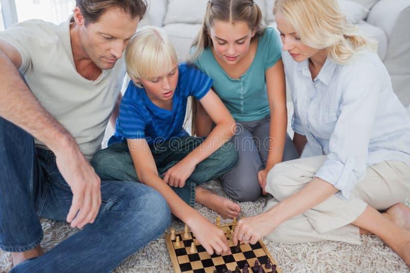 Retrato de uma família bonito que joga a xadrez fotos de stock royalty free