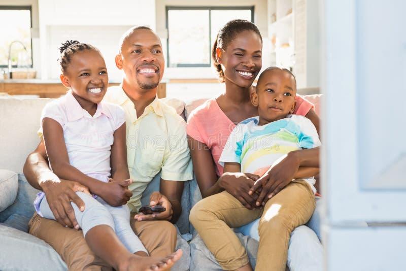 Retrato de uma família de quatro pessoas que olha a tevê imagens de stock