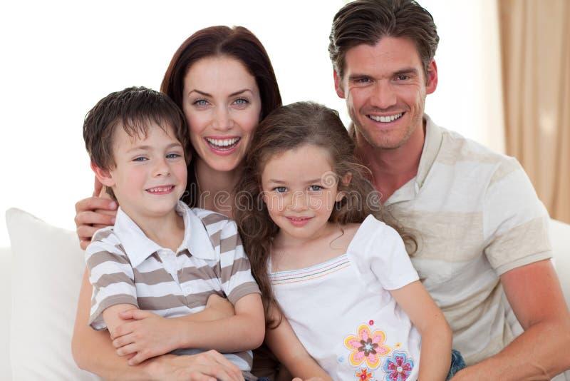 Retrato de uma família de sorriso no sofá imagens de stock
