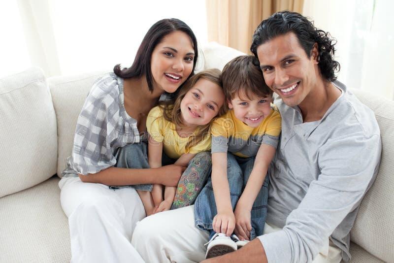 Retrato de uma família de sorriso que senta-se no sofá imagens de stock
