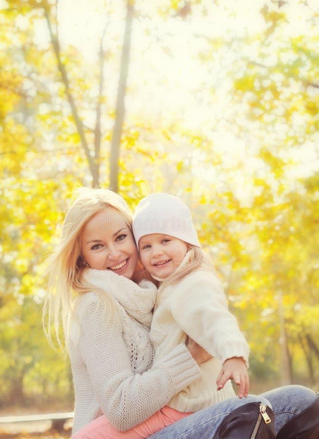 Retrato de uma família feliz com a mãe loura bonita e a filha pequena que descansam no parque fotos de stock royalty free