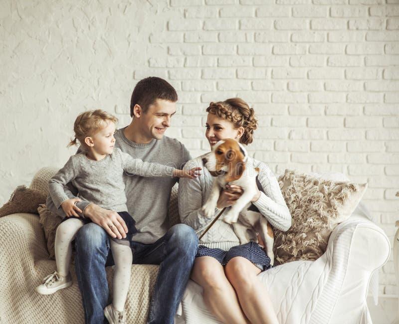 Retrato de uma família feliz e de um animal de estimação que sentam-se em um sofá imagem de stock royalty free