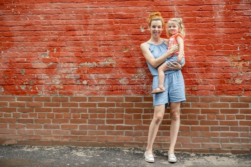 Retrato de uma família feliz uma mulher bonita nova com sua posição bonito pequena da filha perto da parede de tijolo foto de stock royalty free