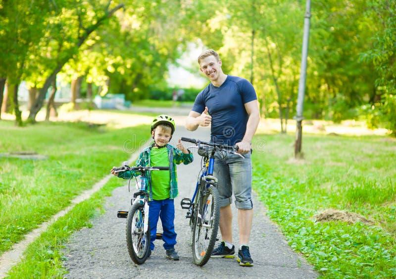 Retrato de uma família feliz - pai e filho que bicycling no parque imagem de stock royalty free