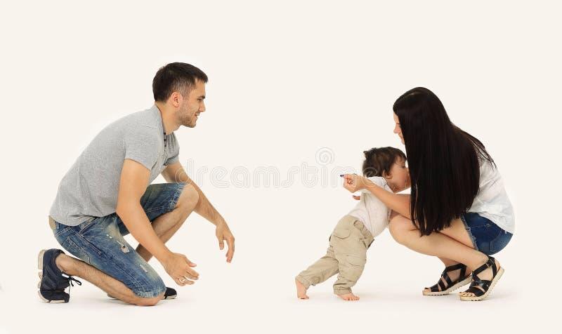 Retrato de uma família feliz que ensine uma criança andar fotografia de stock