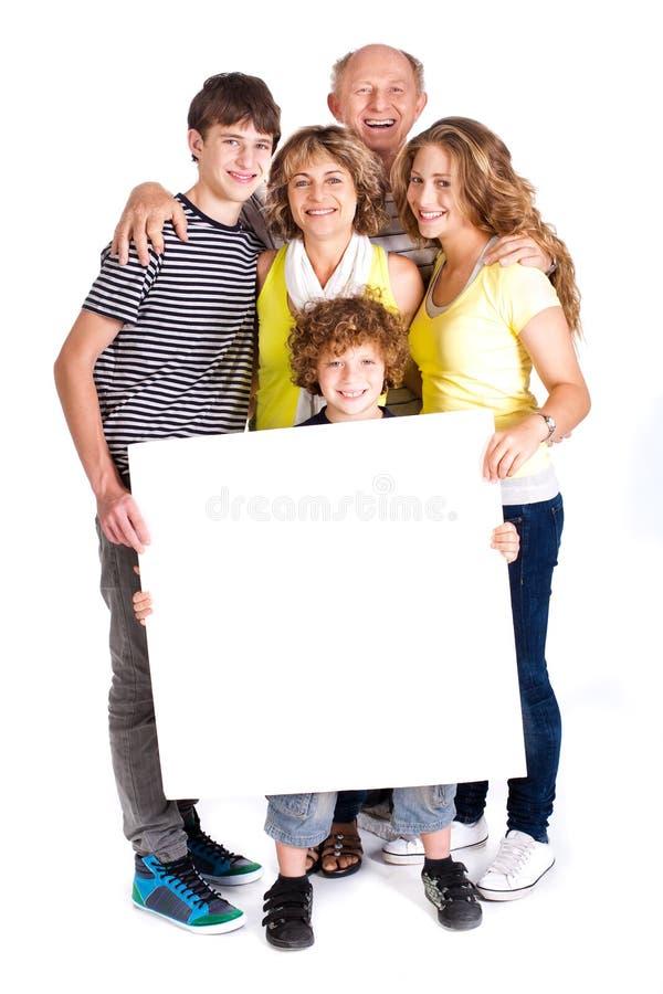 Retrato de uma família feliz que prende um quadro de avisos foto de stock royalty free