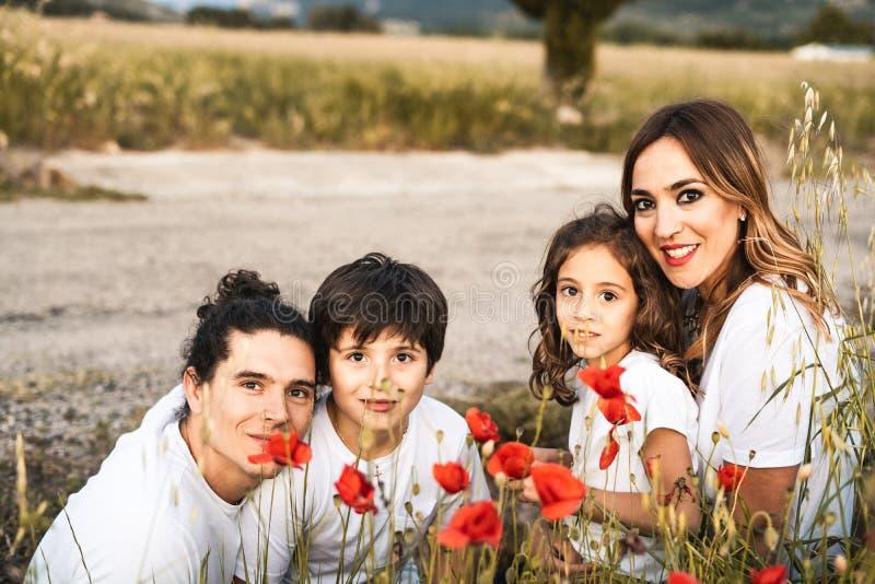 Retrato de uma família nova que sorri e feliz olhando a câmera na parte externa imagem de stock royalty free