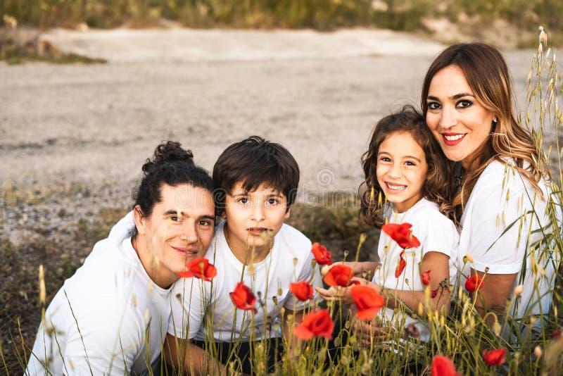 Retrato de uma família nova que sorri e feliz olhando a câmera na parte externa fotografia de stock royalty free